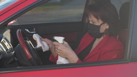 Senior woman disinfecting the steering wheel