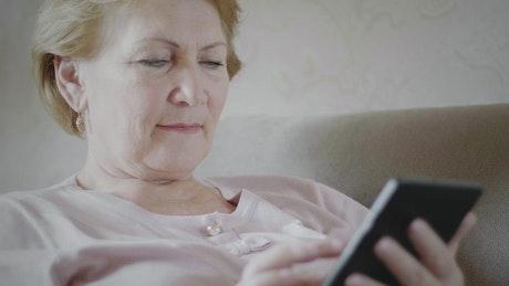 Senior woman looking at reading device