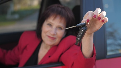 Senior woman showing keys to her new car