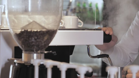 Serving an espresso in a cup of a coffee pot