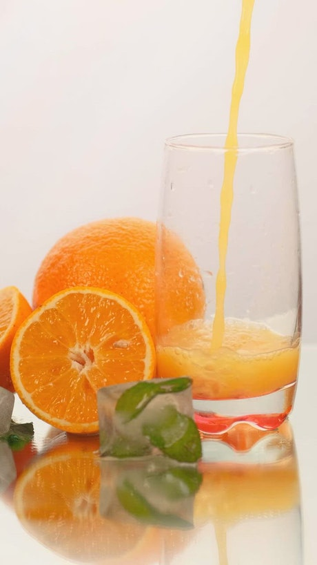 Serving juice in a glass with some oranges on a white background