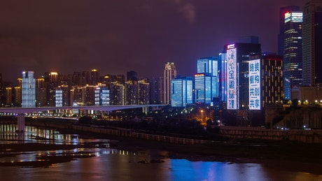 Shining buildings in a city with a river at night