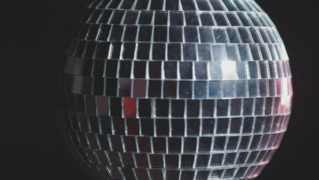 Shiny disco ball spinning with dark background