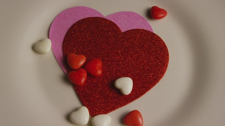 Shiny paper heart shapes and candy