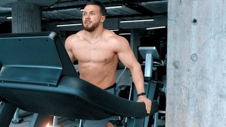 Shirtless bodybuilder running on a treadmill
