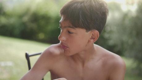 Shirtless boy eating breakfast outside