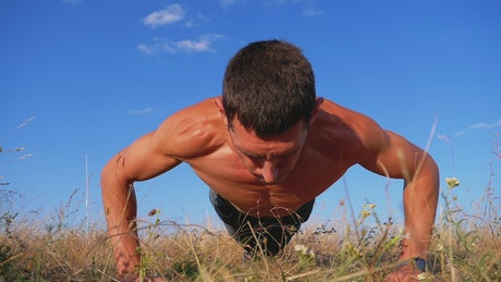 Shirtless man doing push-ups in the countryside
