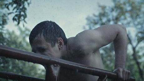 Shirtless man exercises in the rain