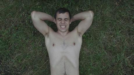 Shirtless man exercising on grass
