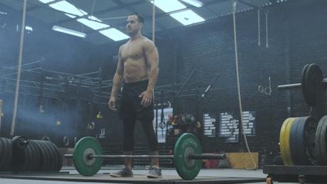 Shirtless man lifting weights at the gym
