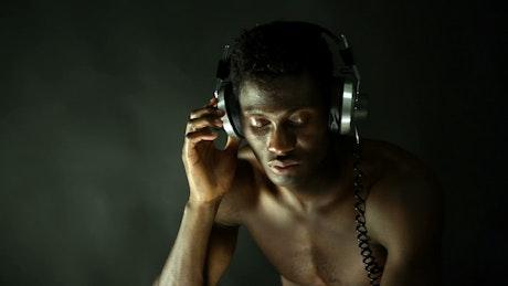 Shirtless man listening to music with retro headphones