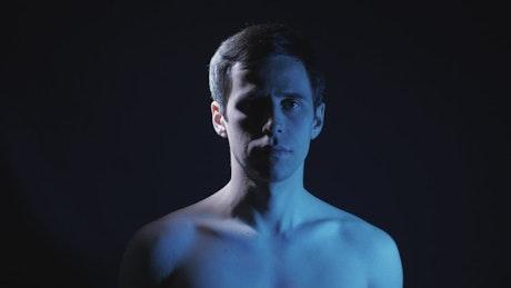 Shirtless man spinning in a dark place