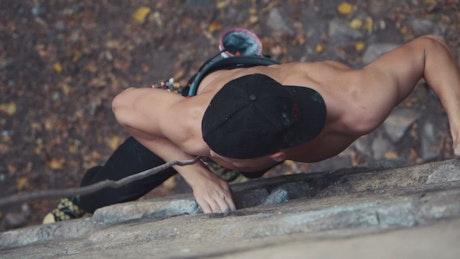 Shirtless young man climbing rock