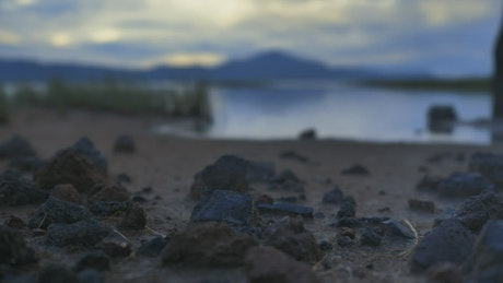 Shore of a calm lake with sand, grass and rocks