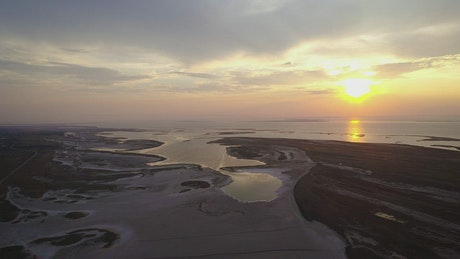 Shore of a huge lake from above at sunset