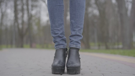 Shot of legs in jeans reveals woman in face mask