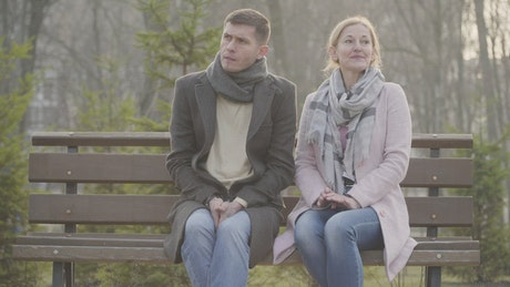 Shy couple sit silent on park bench on cold day