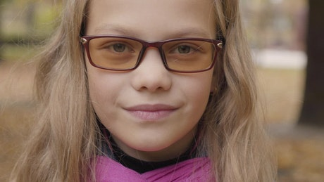 Shy little girl in glasses looks up to camera