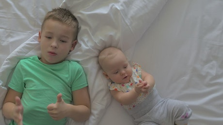 Siblings laying down on a bed