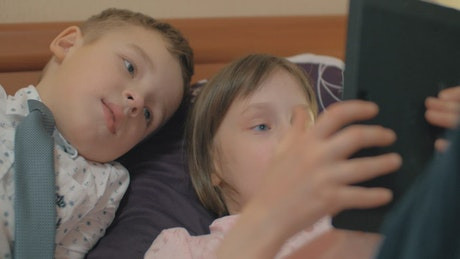 Siblings playing a game on a tablet
