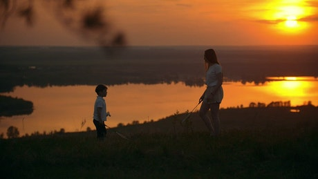 Siblings playing badminton in the sunset