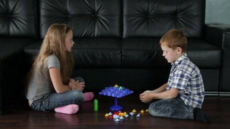 Siblings playing on the floor