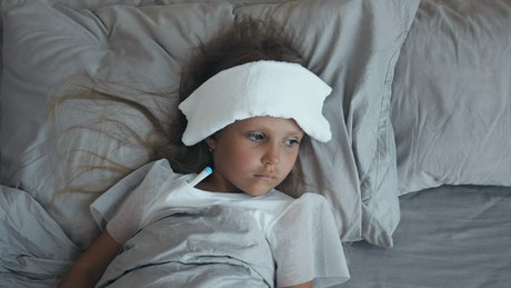 Sick child with a thermometer and a compress