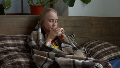 Sick girl sheltered while drinking a tea