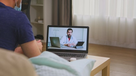 Sick man in video call with doctor during virus lockdown