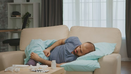 Sick man lays on sofa and looks at medication