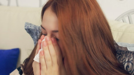 Sick woman sneezing with a tissue