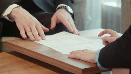 Signing on a contract on a wooden table