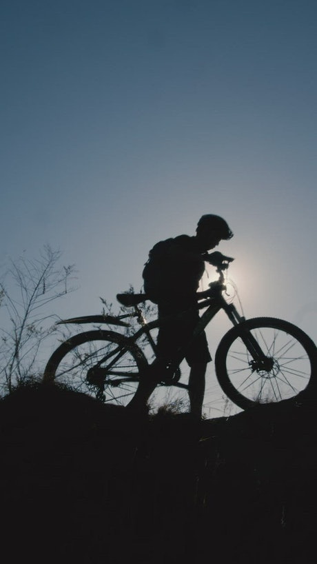 Silhouette in front of the sun of a cyclist outdoors
