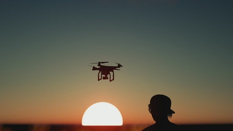 Silhouette of a boy flying a drone at sunset