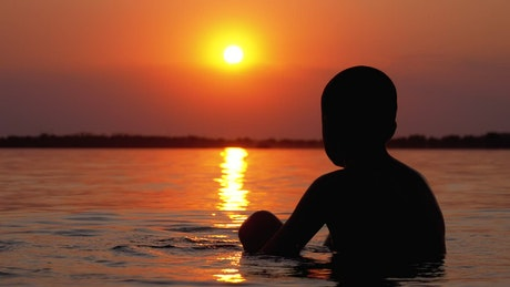 Silhouette of a boy in the sea at sunset