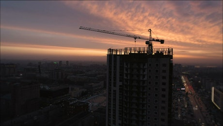 Silhouette of a crane over a build under construction