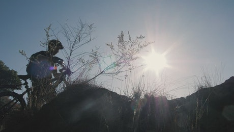 Silhouette of a cyclist in front of the sun in nature