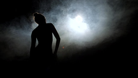Silhouette of a dancer against smoke
