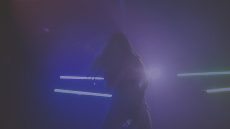 Silhouette of a dancer on a floor with smoke and lights