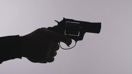 Silhouette of a hand firing a revolver