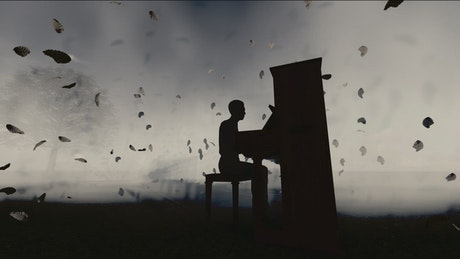 Silhouette of a man playing the piano in the dark