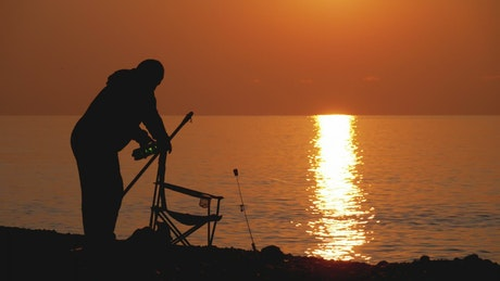 Silhouette of a man preparing chair to fish