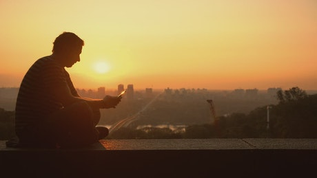 Silhouette of a man texting during the sunset
