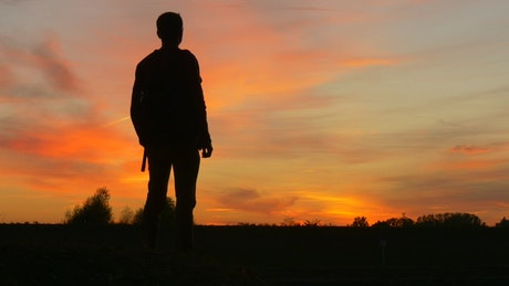 Silhouette of a man with a backpack in the sunset