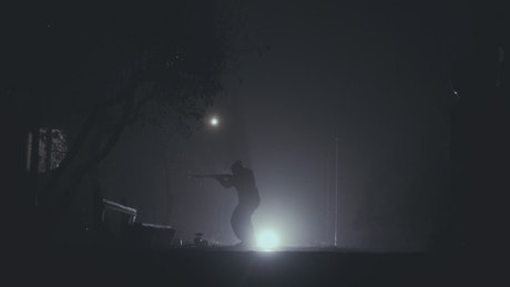 Silhouette of a person with a rifle in the night