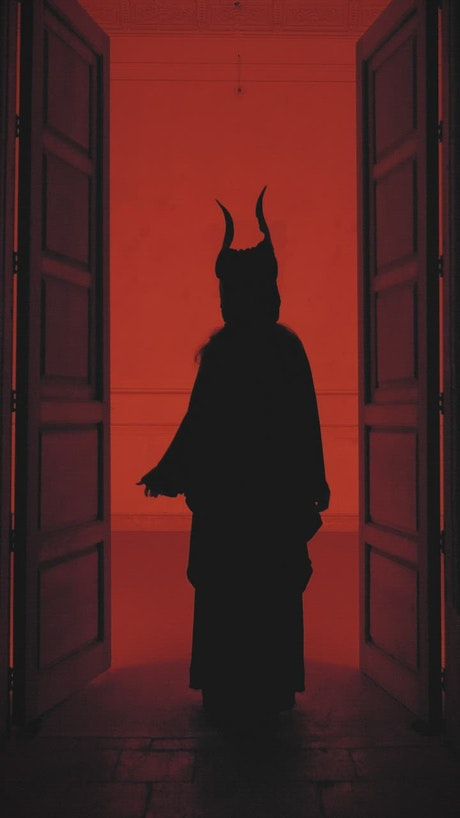 Silhouette of a person with horns and robe under a red light