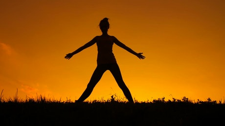 Silhouette of a woman doing yoga during a sunset