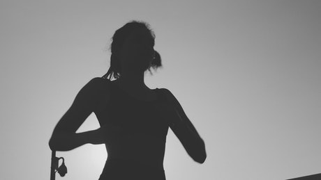 Silhouette of a young woman jogging in front of the sun