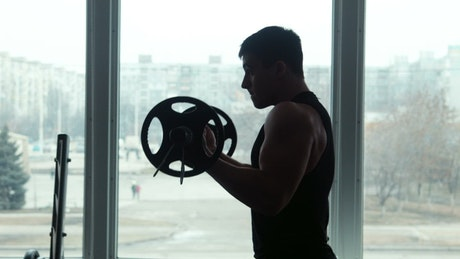 Silhouette of an athlete lifting a barbell
