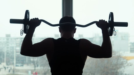 Silhouette of an athlete lifting the barbell